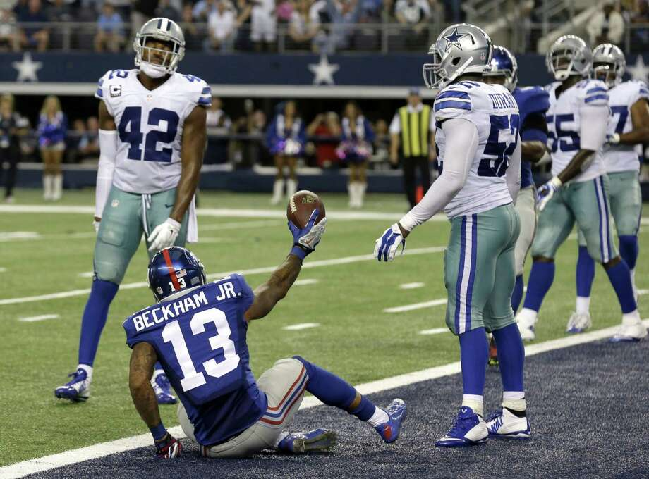 New York Giants rookie receiver Odell Beckham Jr. celebrates his touchdown reception in front of Dallas Cowboys defenders Barry Church (42) and Justin Durant (52) on Sunday in Arlington, Texas. Photo: LM Otero — The Associated Press  / AP