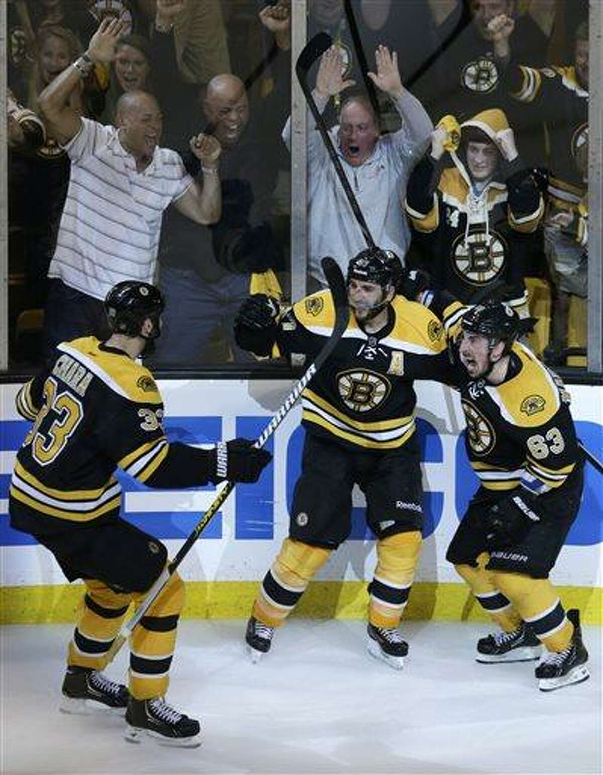 Boston Bruins center Patrice Bergeron, center, is congratulated by teammates Brad Marchand, right, and Zdeno Chara, left, after his game-winning goal against the Pittsburgh Penguins during the second overtime period in Game 3 of the NHL hockey Stanley Cup playoffs Eastern Conference finals, in Boston, Thursday, June 6, 2013. The Bruins won 2-1 and take a 3-0 lead in the series. (AP Photo/Charles Krupa)