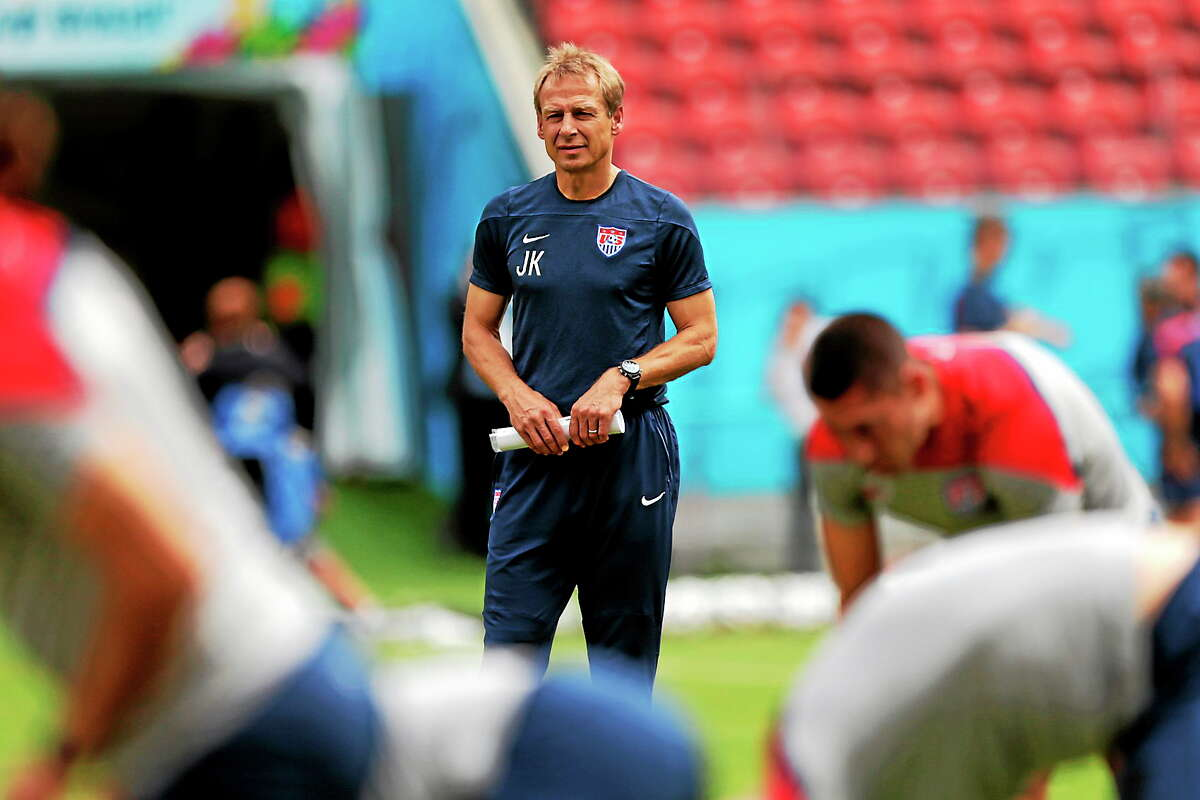 (AP Photo/Julio Cortez) United States' head coach Jurgen Klinsmann watches as his players stretch during a training session in Recife, Brazil on June 25, 2014.