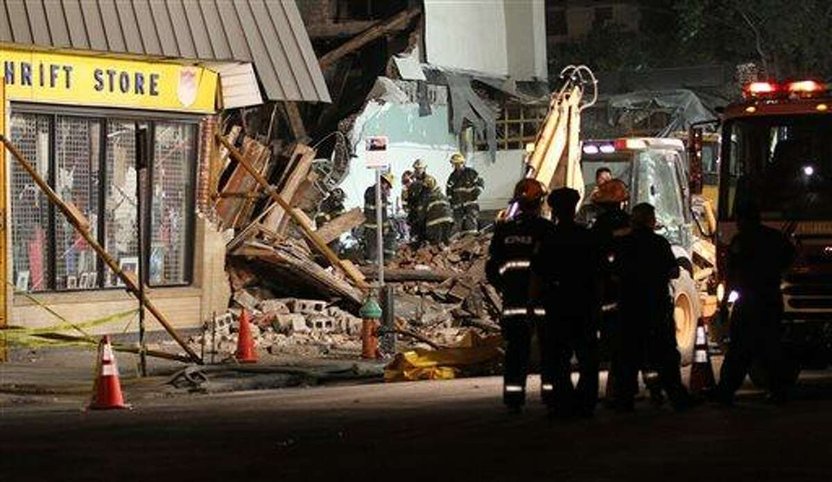 Firefighters stand by while some look for anyone trapped among debris at the site of the collapsed building in Philadelphia, on Wednesday, June 5, 2013. Deputy Fire Chief Robert Coyne said early Thursday that 61-year-old Myra Plekam was pulled from the debris more than 12 hours after a building collapsed and that she was awake and talking to rescuers. She's the 14th survivor of Wednesday's collapse. (AP Photo/Philadelphia Daily News, Stephanie Aaronson)