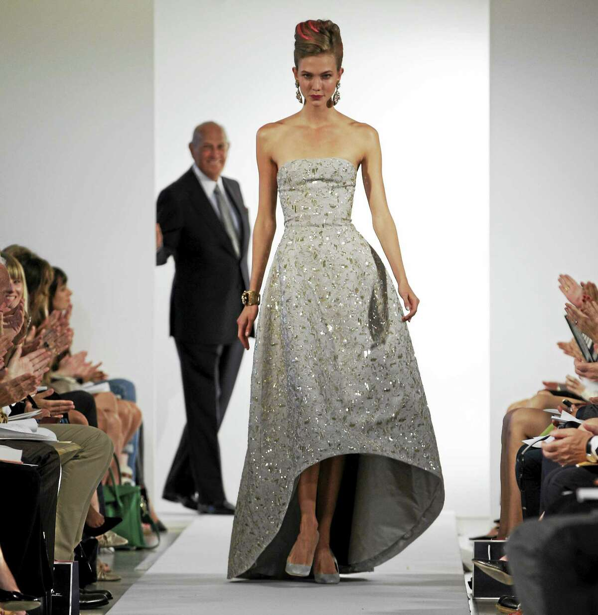 In this Sept. 11, 2012 photo, fashion designer Oscar de la Renta watches as the final model walks the runway during the presentation of his Spring 2013 collection at Fashion Week in New York.