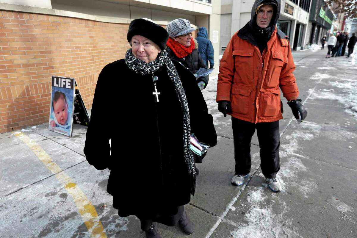 FILE - This Dec. 17, 2013 file photo shows anti-abortion protester Eleanor McCullen, of Boston, left, standing at the painted edge of a buffer zone as she protests outside a Planned Parenthood location in Boston. In a unanimous ruling Thursday, June 26, 2014, the Supreme Court struck down a 35-foot protest-free zone outside abortion clinics in Massachusetts, saying that extending a buffer zone 35 feet from clinic entrances violates the First Amendment rights of protesters. (AP Photo/Steven Senne, File)