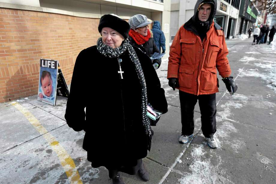 FILE - This  Dec. 17, 2013 file photo shows anti-abortion protester Eleanor McCullen, of Boston, left, standing at the painted edge of a buffer zone as she protests outside a Planned Parenthood location in Boston. In a unanimous ruling Thursday, June 26, 2014, the Supreme Court struck down a 35-foot protest-free zone outside abortion clinics in Massachusetts, saying that extending a buffer zone 35 feet from clinic entrances violates the First Amendment rights of protesters. (AP Photo/Steven Senne, File) Photo: AP / AP