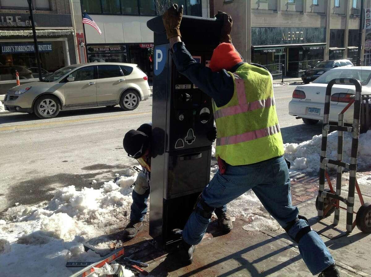 Torrington city workers install one of three new parking kiosks on Main Street Thursday.