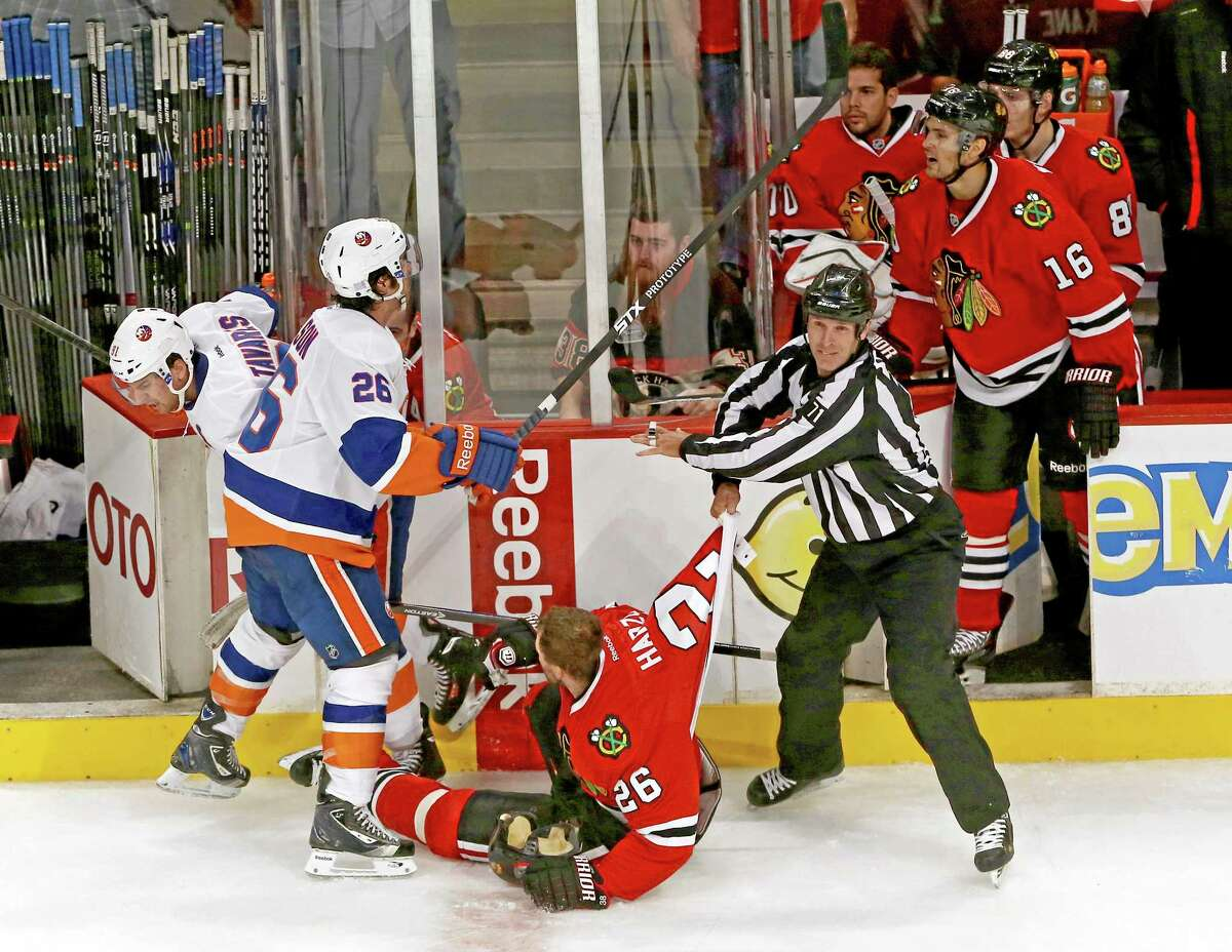Linesman Brad Kovachik pulls the Chicago Blackhawks' Michal Handzus away from the New York Islanders' John Tavares as the Islanders' Matt Moulson gets into a shouting match with the Blackhawks' Marcus Kruger late in the third period. The Blackhawks defeated the Islanders 3-2 on Friday in Chicago.