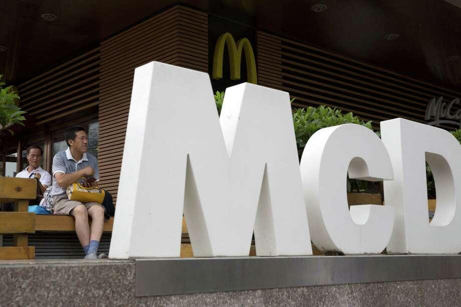 A man rests outside a McDonald's restaurant in Beijing. Photo: Ng Han Guan — The Associated Press  / AP