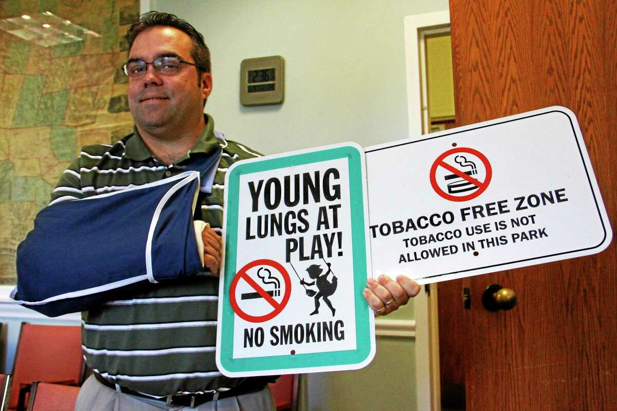 Harwinton First Selectman Michael R. Criss holds up the signs that will soon adorn the town's parks and public spaces Thursday. The signs were paid for with a federal grant.