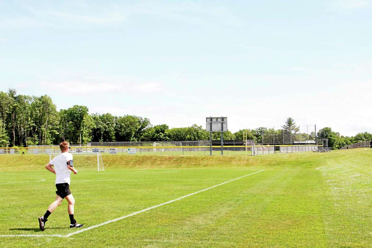 A man runs along a soccer field at the Harwinton Sports Complex Thursday. The public area will be one several to feature the no-smoking signs.