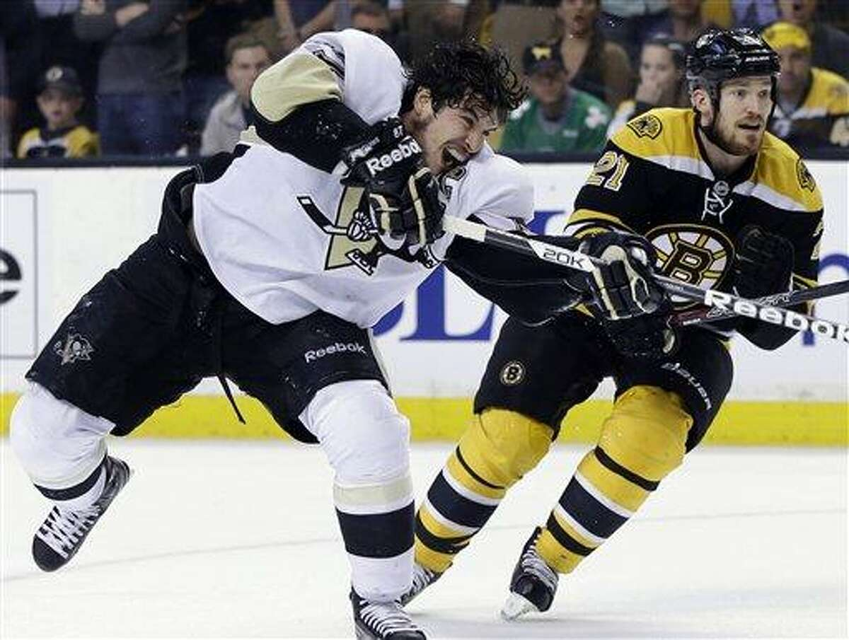 Pittsburgh Penguins center Sidney Crosby (87) shoots the puck as Boston Bruins defenseman Andrew Ference (21) looks on during the second overtime period in Game 3 of the Eastern Conference finals in the NHL hockey Stanley Cup playoffs in Boston, Wednesday, June 5, 2013. (AP Photo/Elise Amendola)