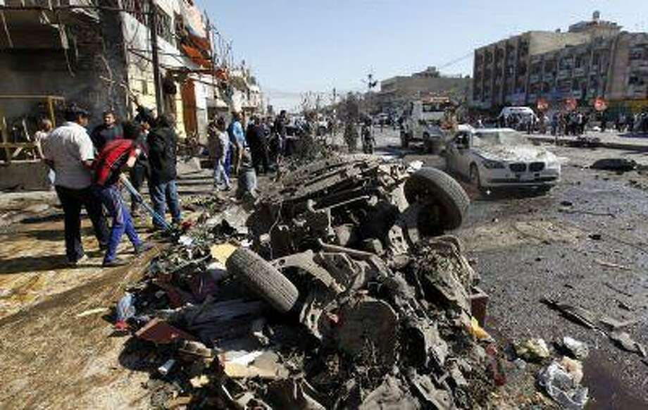 Residents gather at the site of a car bomb attack in the AL-Mashtal district in Baghdad March 19, 2013. A series of coordinated car bombs and blasts hit Shi'ite districts across Baghdad and south of the Iraqi capital on Tuesday, killing at least 25 people on the tenth anniversary of the U.S.-led invasion. REUTERS/Mohammed Ameen (IRAQ - Tags - Tags: CONFLICT CIVIL UNREST TPX IMAGES OF THE DAY) Photo: REUTERS / X01670