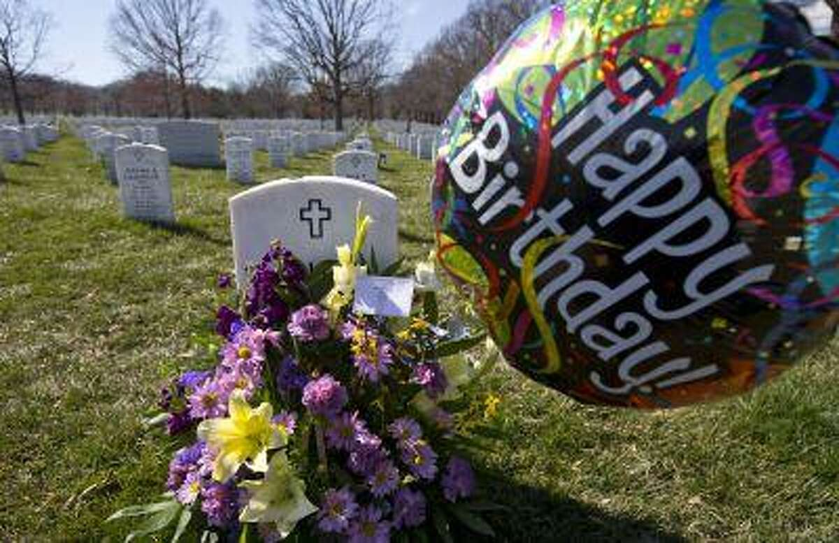Flowers and a happy birthday balloon are placed at the tombstone of Army Sgt. Dale Brehm in Section 60 of Arlington National Cemetery Tuesday, March 19, 2013, in Arlington, Va. Brehm died during the Iraq war. March 20, 2013, marks the 10th anniversary of the U.S.-led invasion of Iraq. (AP Photo/Alex Brandon)