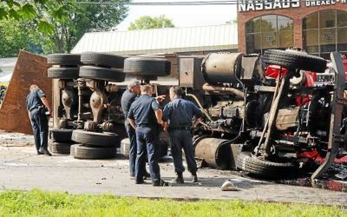 Police inspect an overturned dump truck that collided with a bus causing a chain reaction at the foot of Avon Mountain on Route 44 in Avon, Conn., Friday, July 29, 2005. Several people died and many were hospitalized in the multi-vehicle crash. (AP Photo/Steven Lee Miller)