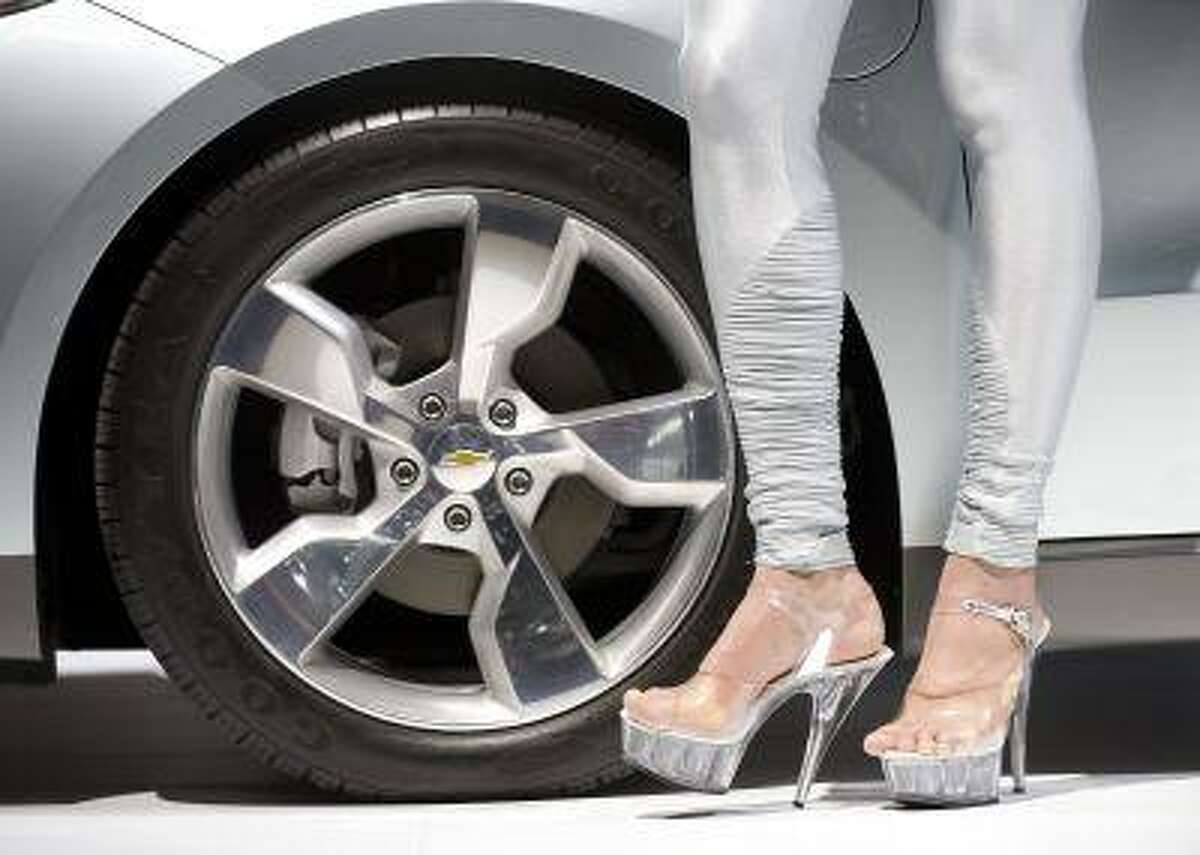 A woman on high heels stands at the wheel of a Chevrolet Volt at an auto show in Geneva, Switzerland.