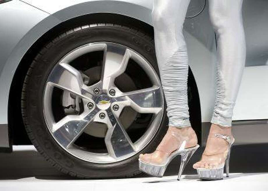 A woman on high heels stands at the wheel of a Chevrolet Volt at an auto show in Geneva, Switzerland. Photo: ASSOCIATED PRESS / AP2010