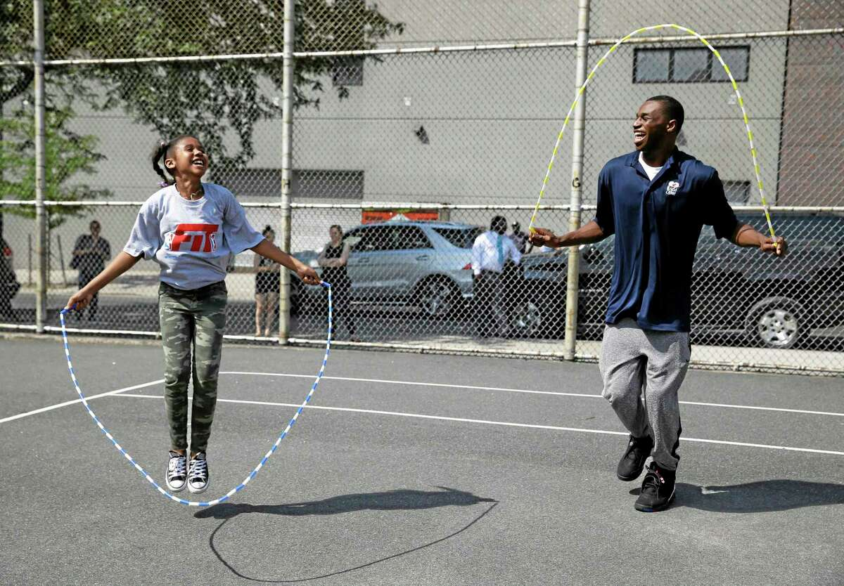 Kansas' Andrew Wiggins jumps rope with a student during a kids basketball clinic on Wednesday in New York.
