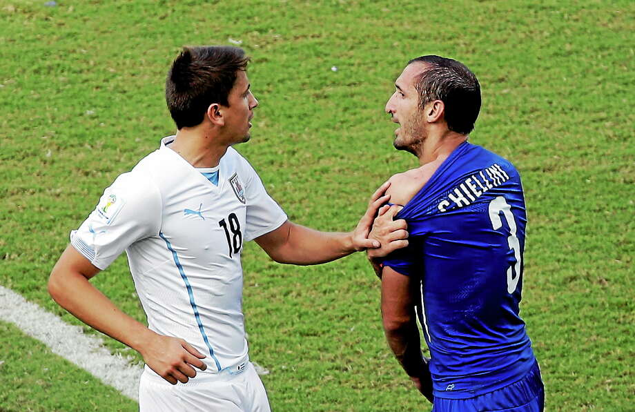 Italy's Giorgio Chiellini (3) complains after Uruguay's Luis Suarez ran into his shoulder with his teeth during the group D World Cup soccer match between Italy and Uruguay at the Arena das Dunas in Natal, Brazil on June 24, 2014. Photo: AP Photo/Hassan Ammar  / AP2014