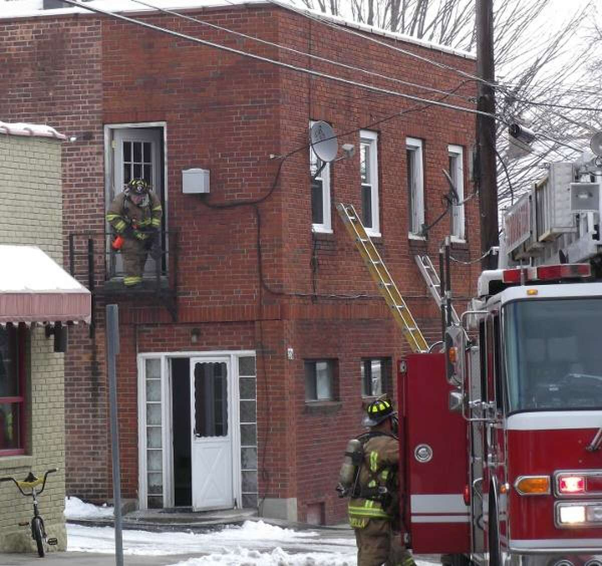 A fireman prepares to go through building to check to make sure the fire is out.