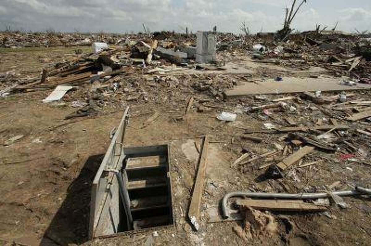 An underground shelter is seen among tornado rubble Sunday, May 26, 2013, in Moore, Okla. A strong tornado ripped through the community Monday, May 20, 2013, flattening a wide swath of homes and businesses. (AP Photo/Charlie Riedel)