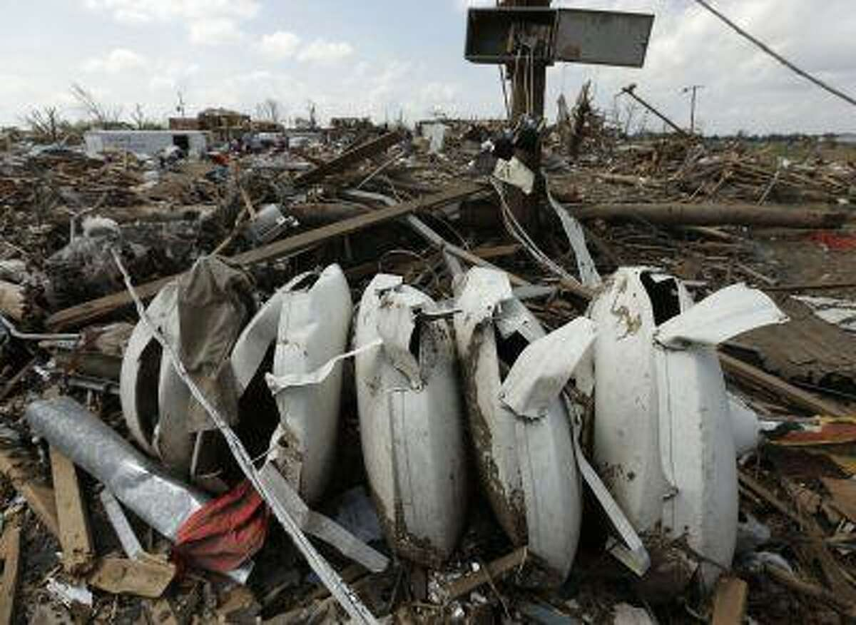 A destroyed warning siren is seen in tornado rubble Sunday, May 26, 2013, in Moore, Okla. A strong tornado ripped through the community Monday, May 20, 2013, flattening a wide swath of homes and businesses. (AP Photo/Charlie Riedel)