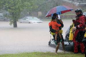 A man and child leave from a rescue boat to transfer to a pickup area along Edgebrook Sunday, August 27, 2017. Much of the area is flooded from rains after Hurricane Harvey.