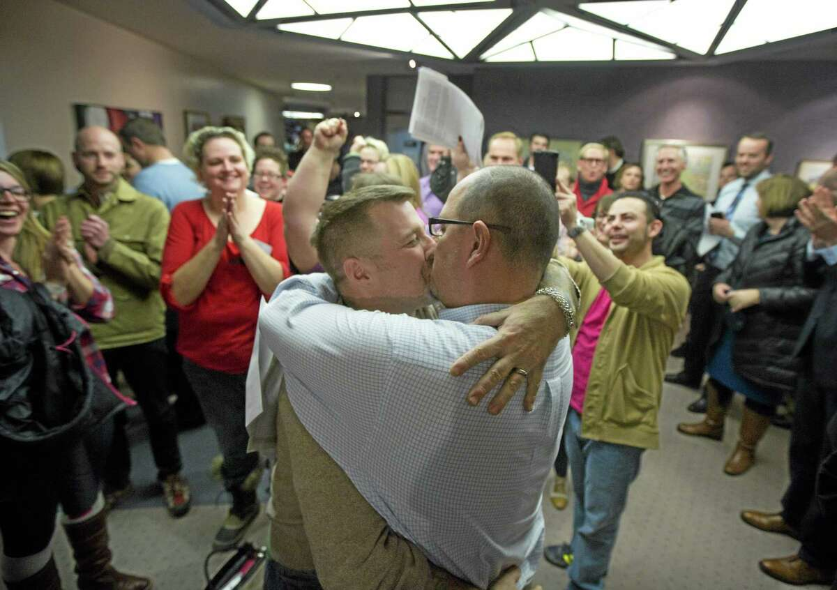 In this Dec. 20, 2013 file photo, Chris Serrano, left, and Clifton Webb kiss after being married, as people wait in line to get licenses outside of the marriage division of the Salt Lake County Clerk's Office, in Salt Lake City. On Wednesday, a federal appeals court ruled for the first time that states must allow gay couples to marry, finding the Constitution protects same-sex relationships and putting a remarkable legal winning streak across the country one step closer to the U.S. Supreme Court. The decision from a three-judge panel in Denver upheld a lower court ruling that struck down Utah's gay marriage ban.