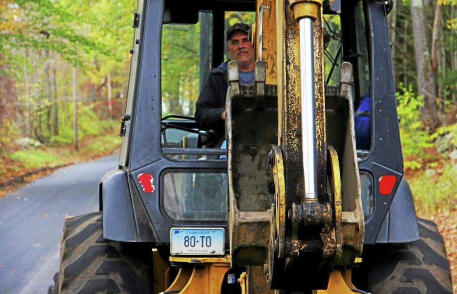 Equipment operator Troy LaMere lifts the excavatpr claw of the backhoe due for replacement on Monday on Weigold Road in Torrington. Photo: Esteban L. Hernandez — Register Citizen