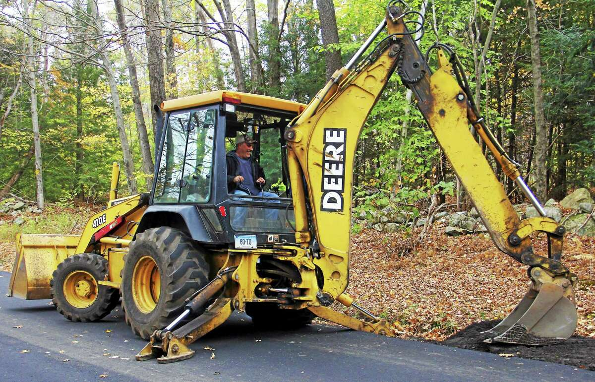 Equipment operator Troy LaMere uses the backhoe due for replacement on Monday on Weigold Road in Torrington. City crews were working on some minor road repairs.