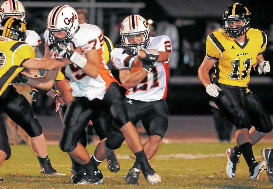 (Mara Lavitt — New Haven Register) September 27, 2013 Woodbridge.Shelton at Amity football. Shelton's Jason Thompson on the carry, with #75 Christopher Pawlowski blocking. Amity's Benjamin Feola at right. For more photos visit photos.GameTimeCT.com or photos.newhavenregister.com Photo: Journal Register Co. / Mara Lavitt