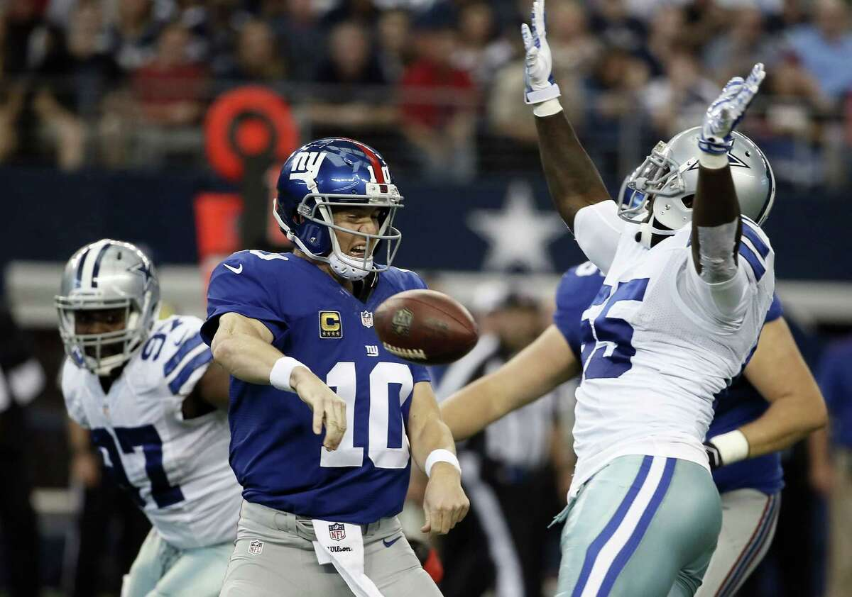Giants quarterback Eli Manning (10) has his pass broken up by the Cowboys' Rolando McClain (55) during the first half Sunday.