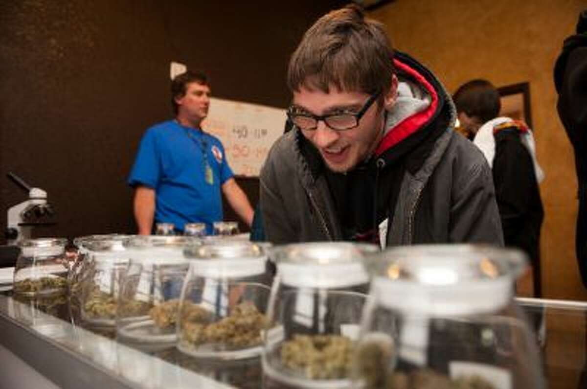 Tyler Williams of Blanchester, Ohio inspects pot for sale at a Denver dispensary.