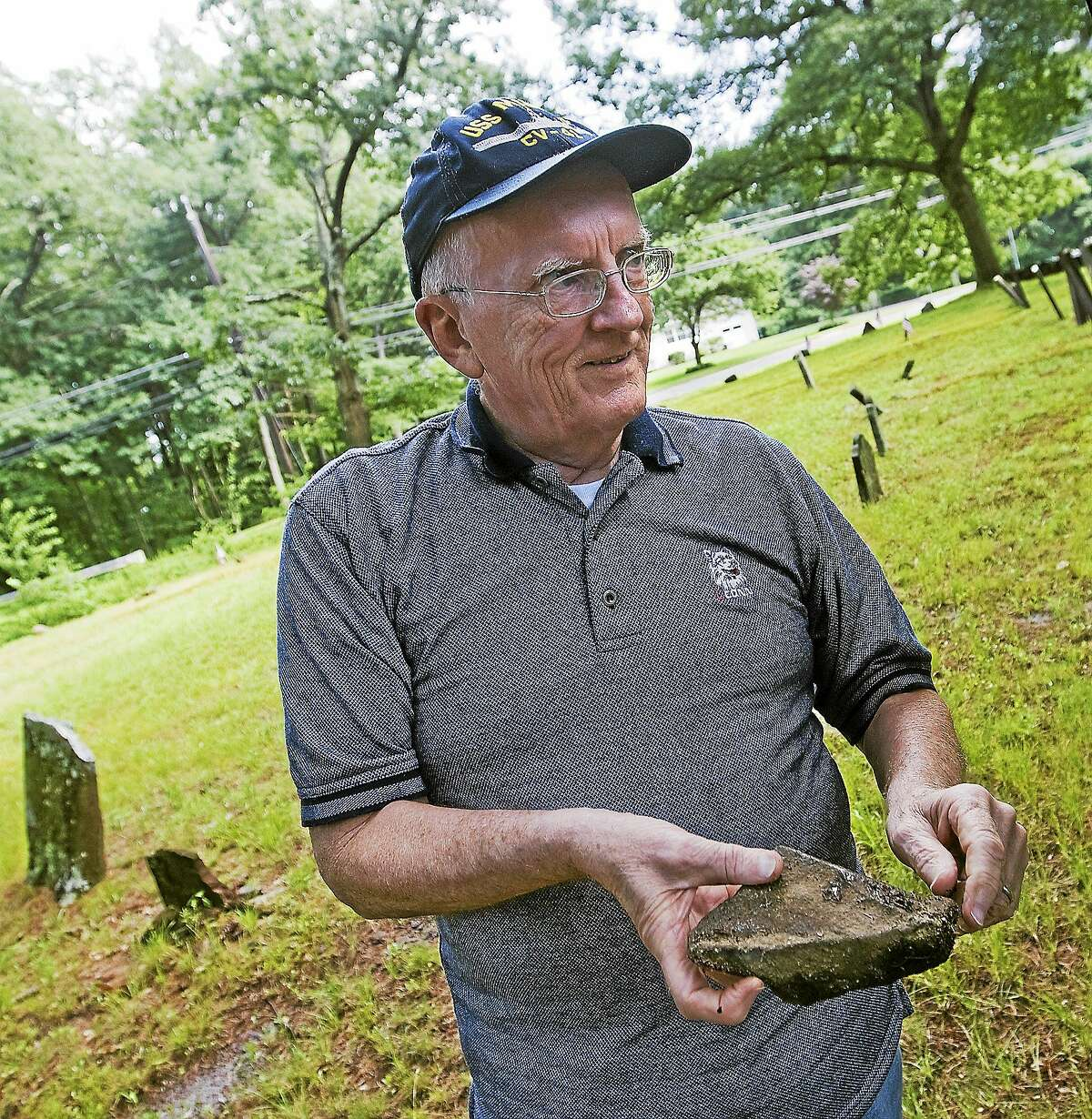 In this July 9, 2013 photo, Ray Thomas, co-founder of the Southington Genealogy Society, holds a stone from a broken memorial at Merriman Burying Ground in Plantsville, Conn.