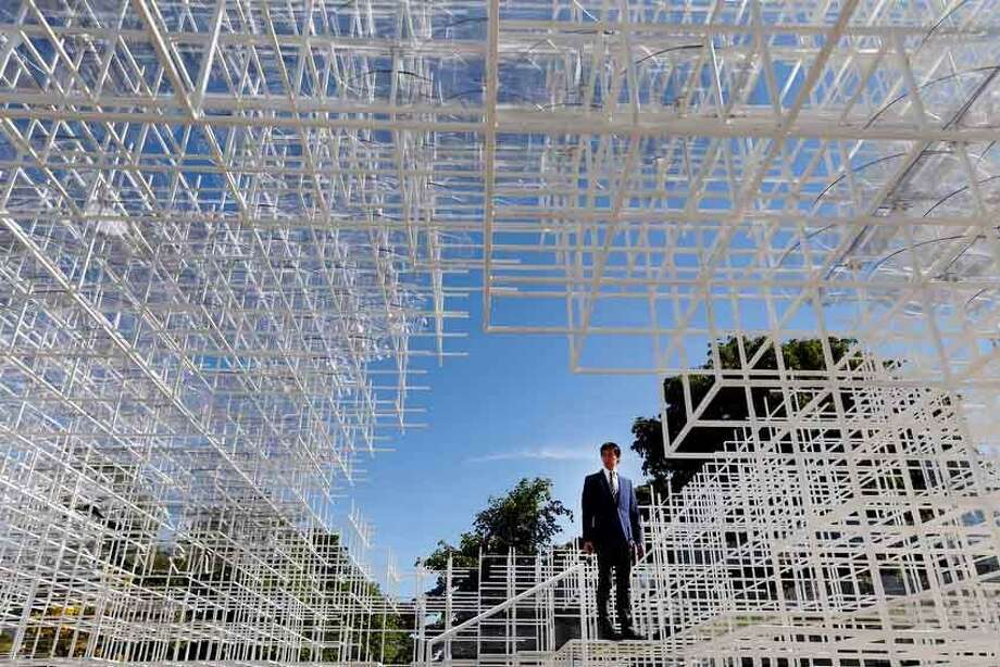 A broadcast journalists stands inside the Serpentine Gallery 2013 Pavilion, designed by Japanese architect Sou Fujimoto, in central London's Kensington Gardens, Tuesday, June 4, 2013. Occupying some 357 square-meters of lawn in front of the Serpentine Gallery, 41-year-old Fujimoto's structure of 20mm steel poles features a cafe and visitors will be encouraged to enter and interact with the piece in different ways. (AP Photo/Lefteris Pitarakis) Photo: ASSOCIATED PRESS / AP2013