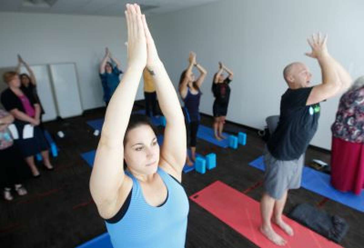 In this photo taken Tuesday, Sept. 17, 2013, Rebecca Nielsen participates in an introductory yoga class at the Blue Cross Blue Shield of Tennessee fitness center in Chattanooga, Tenn.