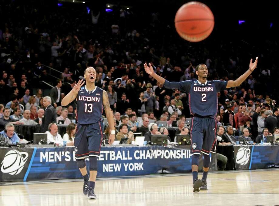 Connecticut's Shabazz Napier (13) and DeAndre Daniels (2) gesture to their teammates during the second half of a regional final against Michigan State in the NCAA college basketball tournament, Sunday, March 30, 2014, in New York. Connecticut won 60-54. (AP Photo/Frank Franklin II) Photo: AP / AP