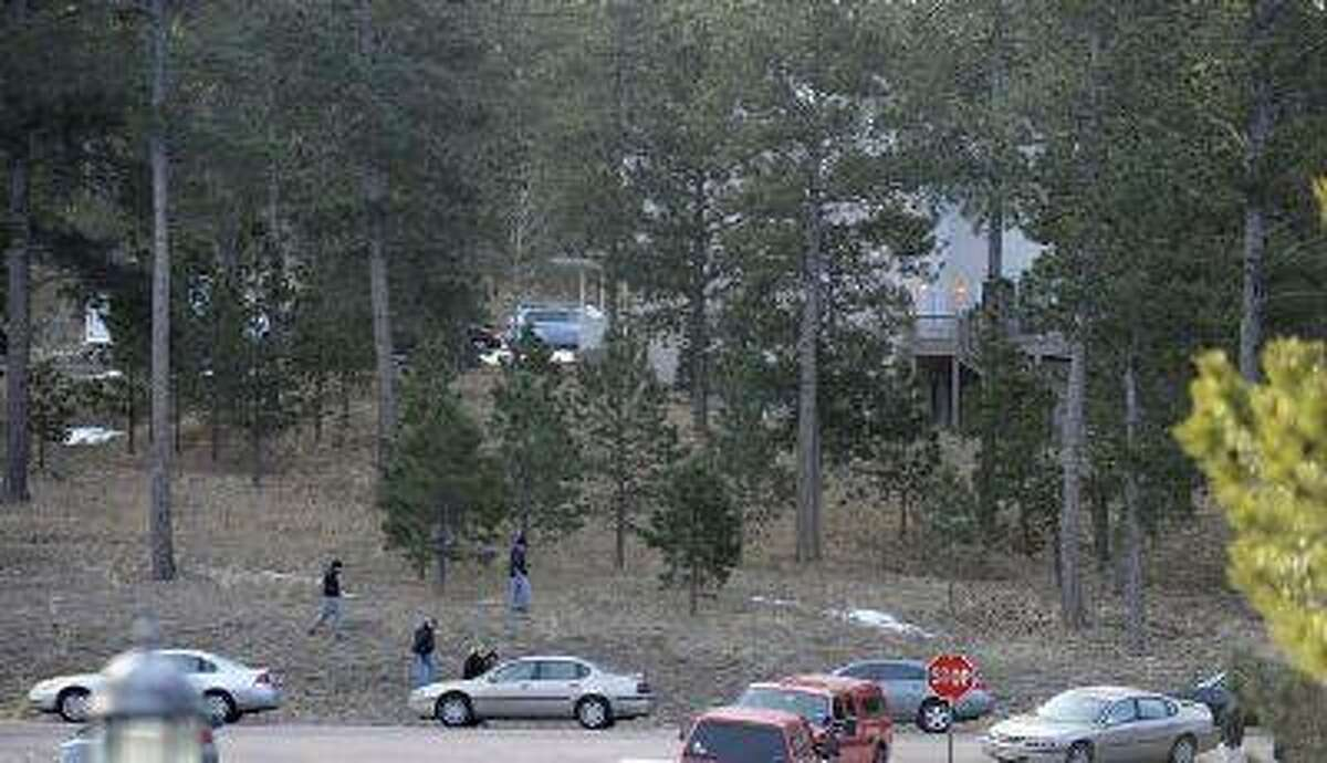 Investigators search the area surrounding the home of Tom Clements, executive director of the Colorado Dept. of Corrections on Colonial Park Drive, east of Monument Wednesday morning, March 20, 2013.