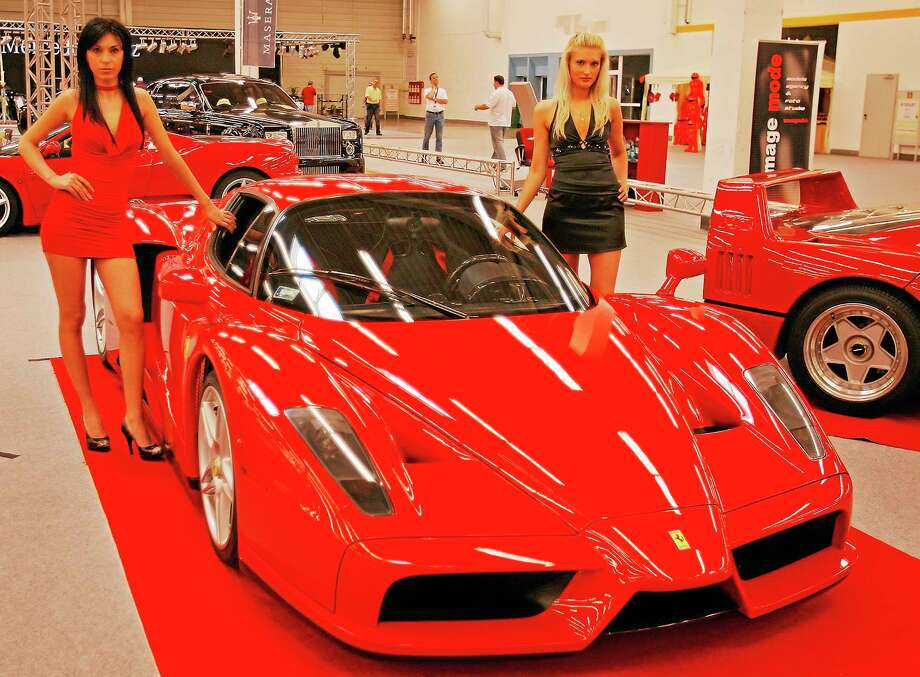 Models stand by a Ferrari Enzo, the type of car involved in crash Monday morning on Interstate 95 in Stamford, Conn. Photo: AP Photo/Vadim Ghirda  / AP2007
