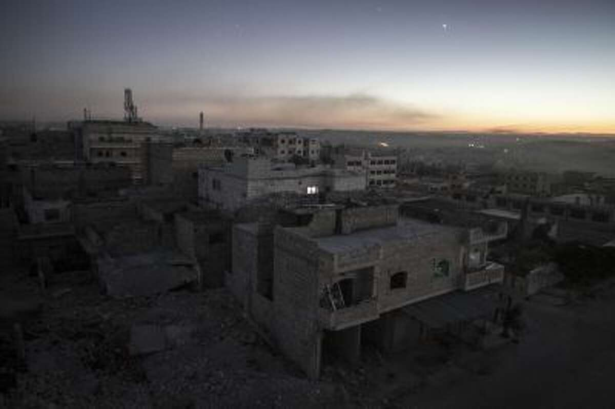 Smoke from burning tires set by opposition fighters overcasts what it used to be a residential area during their fighting against Syrian government forces in Maaret al-Numan in the Idlib province, Syria, Oct. 9.