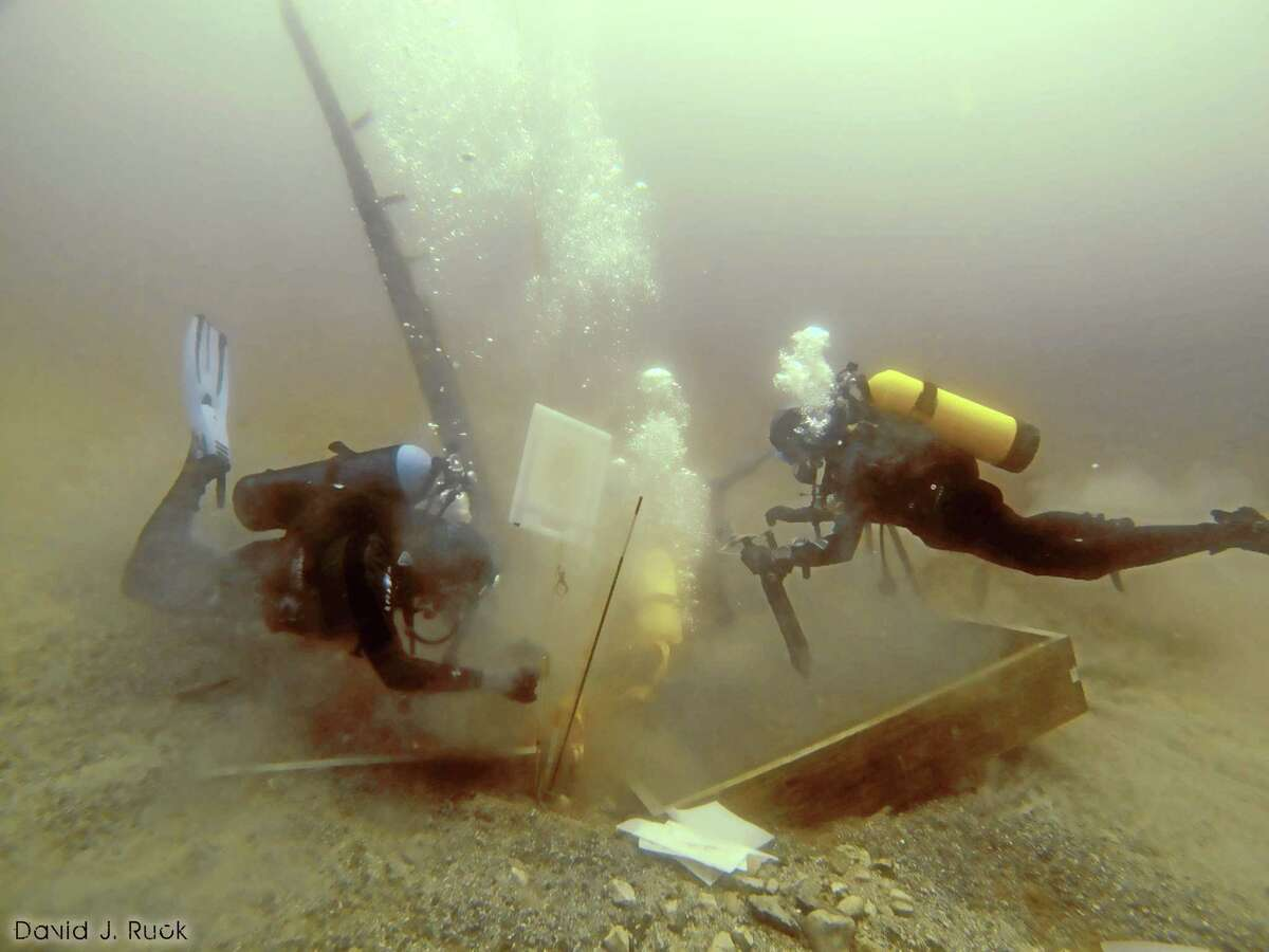 FILE - In this June 16, 2013 photo provided by Great Lakes Exploration Group, divers inspect a hole being dug beside a wooden beam jutting from the floor of Lake Michigan during exploration for the 17th century ship the Griffin. A debris field at the bottom of Lake Michigan may be the remains of the long-lost Griffin, a vessel commanded by a 17th-century French explorer, said a shipwreck hunter who has sought the wreckage for decades. Steve Libert told The Associated Press that his crew found the debris this month about 120 feet from the spot where they removed a wooden slab a year ago that was protruding from the lake bottom. (AP Photo/Great Lakes Exploration Group, David J. Ruck, File)