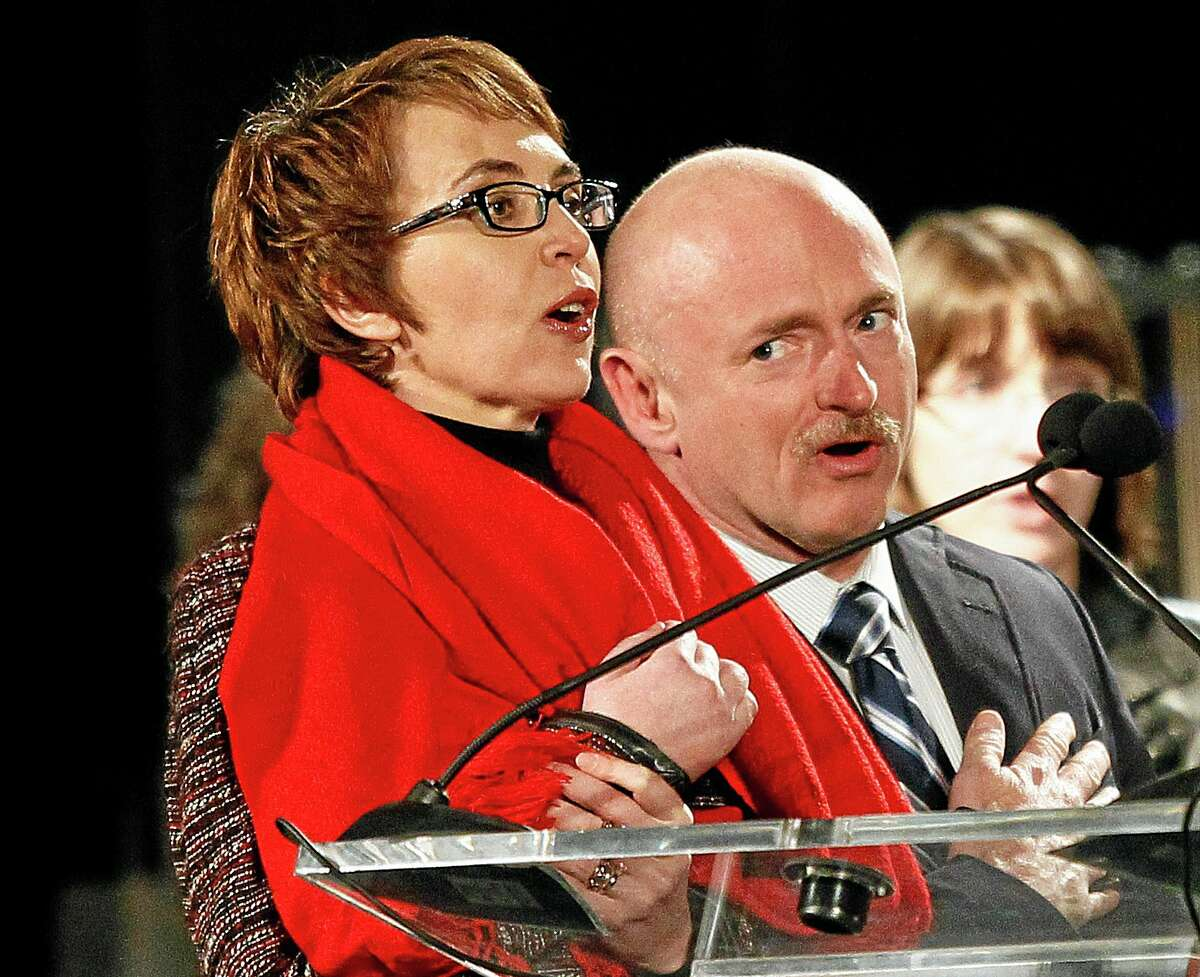 FILE - Rep. Gabrielle Giffords, left, leads the Pledge of Allegiance accompanied by her husband, former astronaut Mark Kelly, at the start of a one year memorial vigil for the victims and survivors of the shooting that wounded Giffords, 12 others and killed six in this Sunday, Jan. 8, 2012 file photo taken in Tucson, Ariz. The three-year anniversary of the shooting of Gabrielle Giffords will be marked Wednesday Jan. 8, 2013 with bell-ringing, flag-raising and other ceremonies, providing a moment of reflection for the former congresswoman. Giffords and Kelly plan to mark the anniversary privately with friends and other survivors of the attack. (AP Photo/Matt York, File)