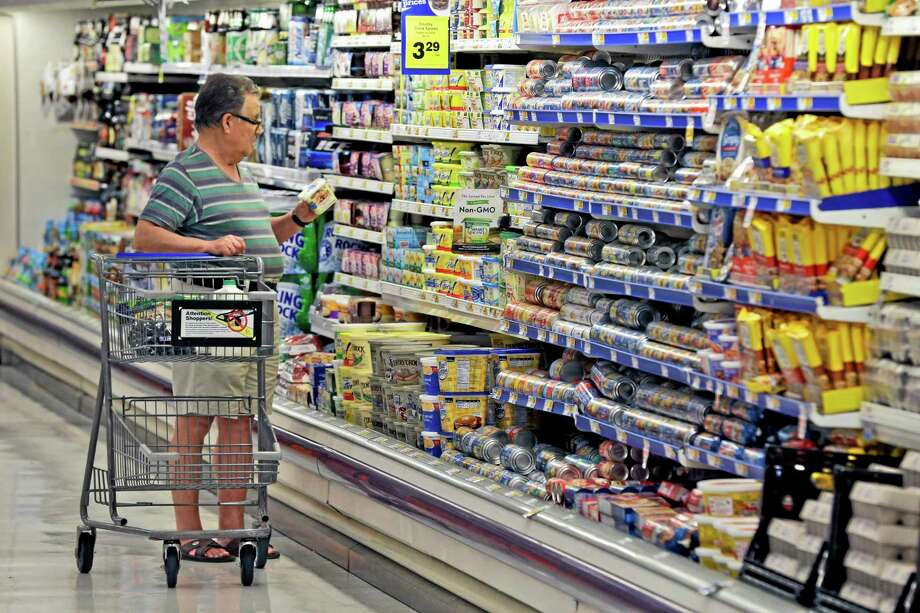 In this June 17, 2014 photo, a shopper looks at an item in the dairy section of a Kroger grocery store in Richardson, Texas. The Conference Board releases the Consumer Confidence Index for June on Tuesday, June 24, 2014. (AP Photo/LM Otero) Photo: AP / AP