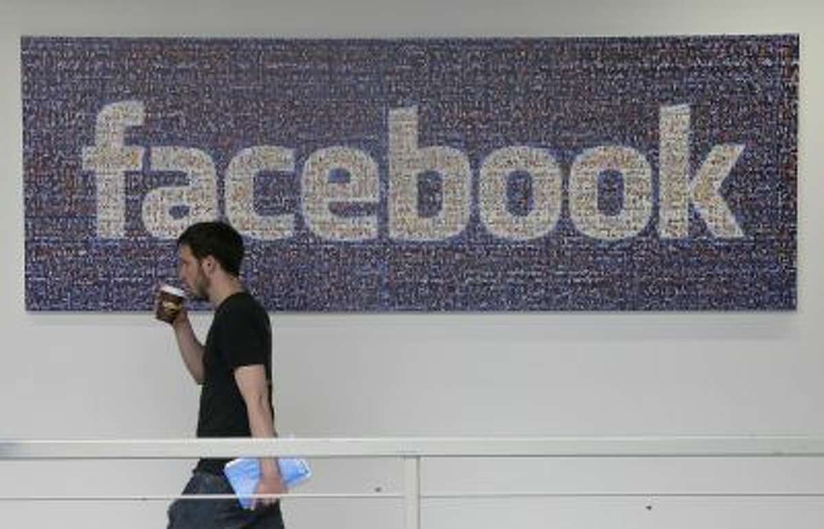 In this March 15, 2013 photo, a Facebook employee walks past a sign at Facebook headquarters in Menlo Park, Calif.