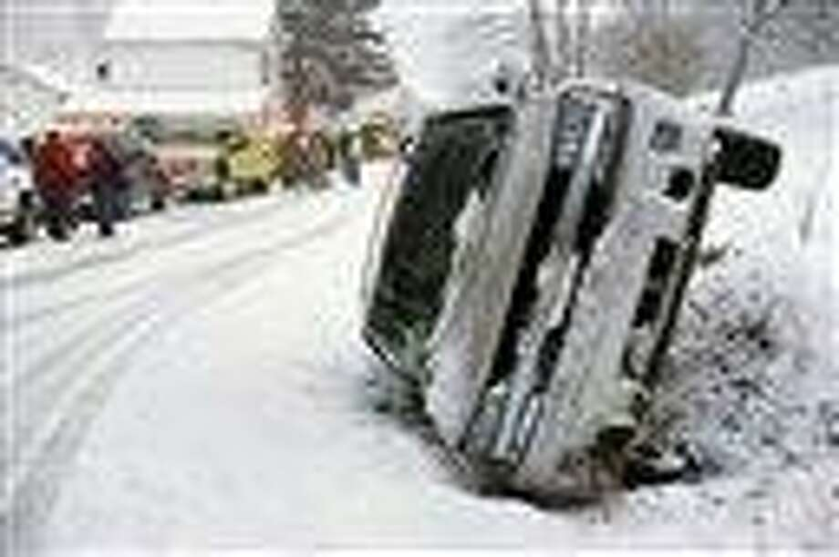 A Chevrolet Blazer went into a ditch and rolled onto its passenger side on a snow-covered Cherry Street in Rockefeller Township, Northumberland County, Pa. on Monday, March 18, 2013.  A mother and daughter escaped injury State police at Stonington did not provide any additional information. (AP Photo/The News-Item, Larry Deklinski) Photo: AP / The News-Item