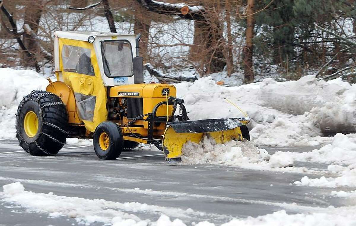 Marc Collins, a Branford Board of Education employee, plows slush and snow in the parking lot of the Walsh Intermediate School onto existing piles of snow before the start of school Tuesday morning. Rather than cancel, many schools in the New Haven area had delays. Photo by Peter Hvizdak / New Haven Register