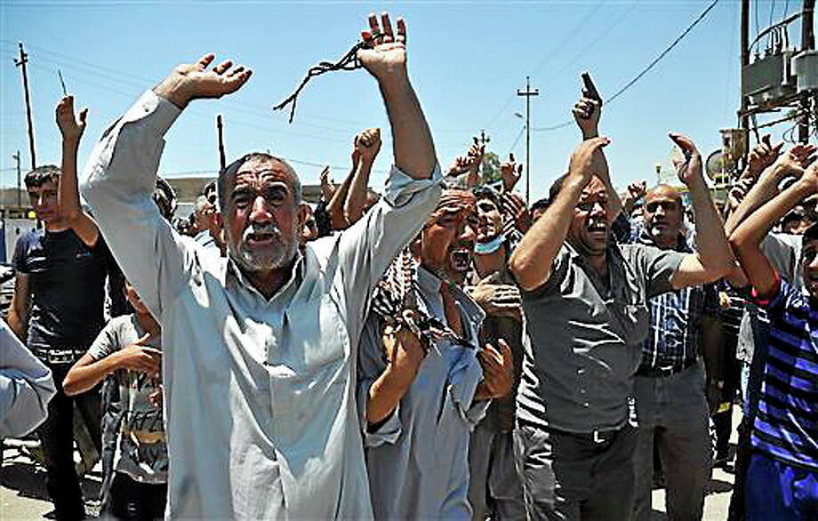 In this June 23, 2014, photo, mourners chant slogans against the al-Qaida breakaway group Islamic State of Iraq and the Levant after they bury 15 bodies in the village of Taza Khormato near the northern oil-rich city of Kirkuk, Iraq. U.S. teams of special forces going into Iraq after a three-year gap will face an aggressive insurgency, a splintering military and a precarious political situation as they help Iraqi security forces improve their ability to battle Sunni militants. (AP Photo/Emad Matti) Photo: AP / AP