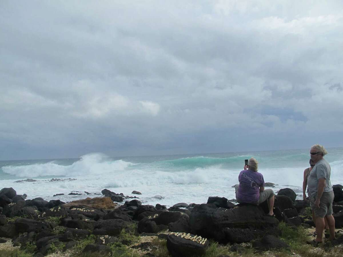 People watch high surf at South Point, Hawaii on Friday, Oct. 17, 2014 as Hurricane Ana carved a path just south of the island state. The storm prompted a flood advisory and winds strong enough for officials to urge caution. (AP Photo/Audrey McAvoy)