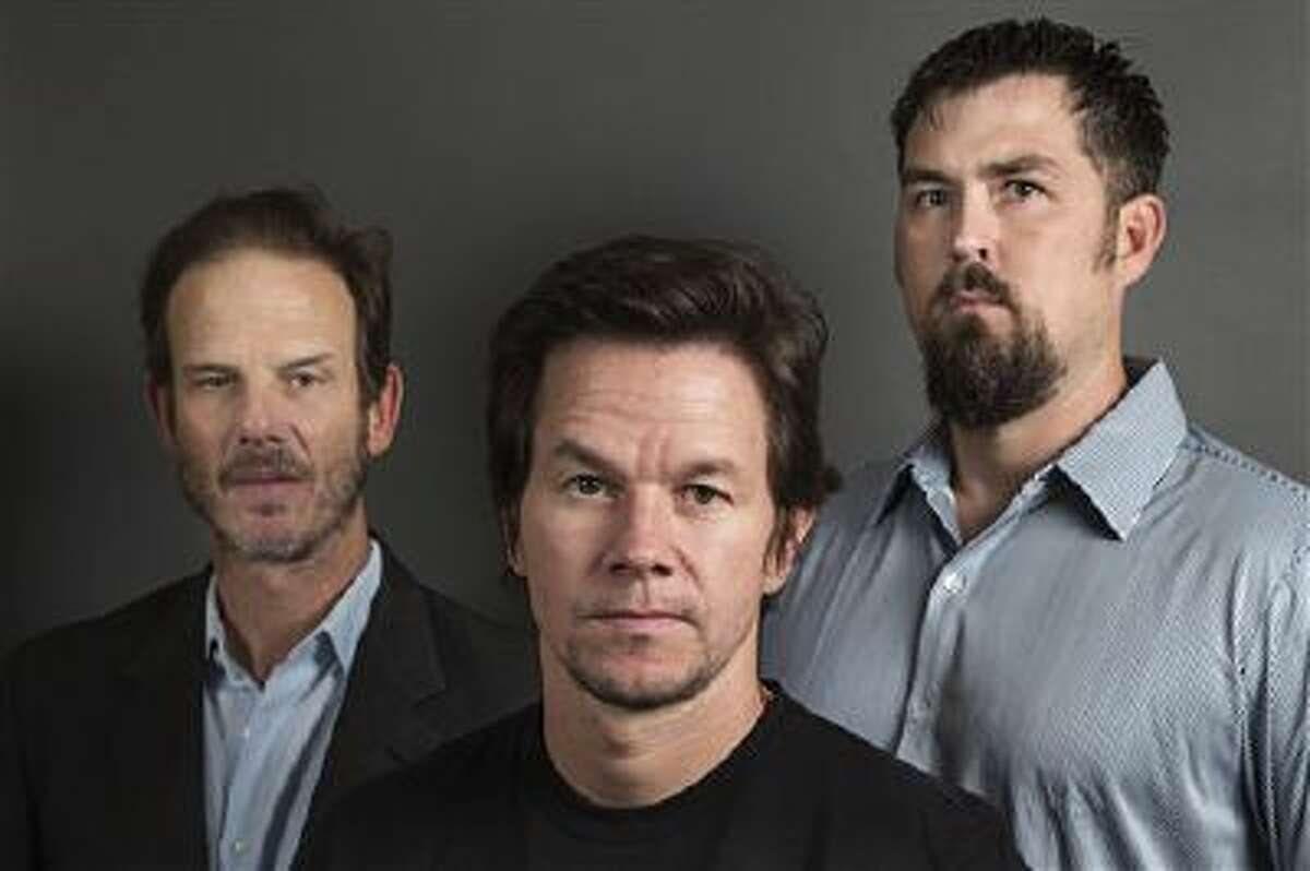 """This Dec. 5, 2013 photo shows director Peter Berg, from left, actor Mark Wahlberg and former Navy SEAL Marcus Luttrell in New York. In the age of the superhero, the movies' most reliable real-life hero has been the Navy SEAL. """"Lone Survivor,"""" starring Mark Wahlberg, is the latest in a string of films, including """"Zero Dark Thirty"""" and """"Act of Valor"""" to honor the Navy's special operations force with as much faithfulness as the filmmakers could muster."""