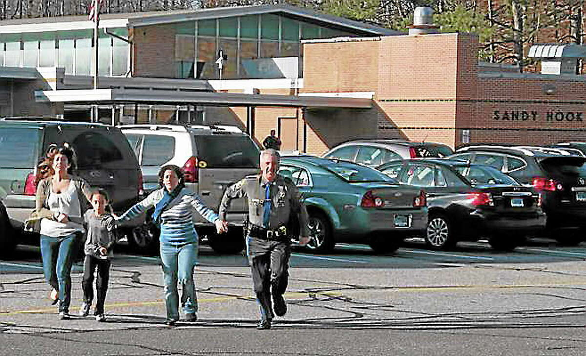 FILE - In this Dec. 14, 2012, file photo provided by the Newtown Bee, a police officer leads two women and a child from Sandy Hook Elementary School in Newtown, Conn., where a gunman opened fire, killing 26 people, including 20 children. (AP Photo/Newtown Bee, Shannon Hicks, File)