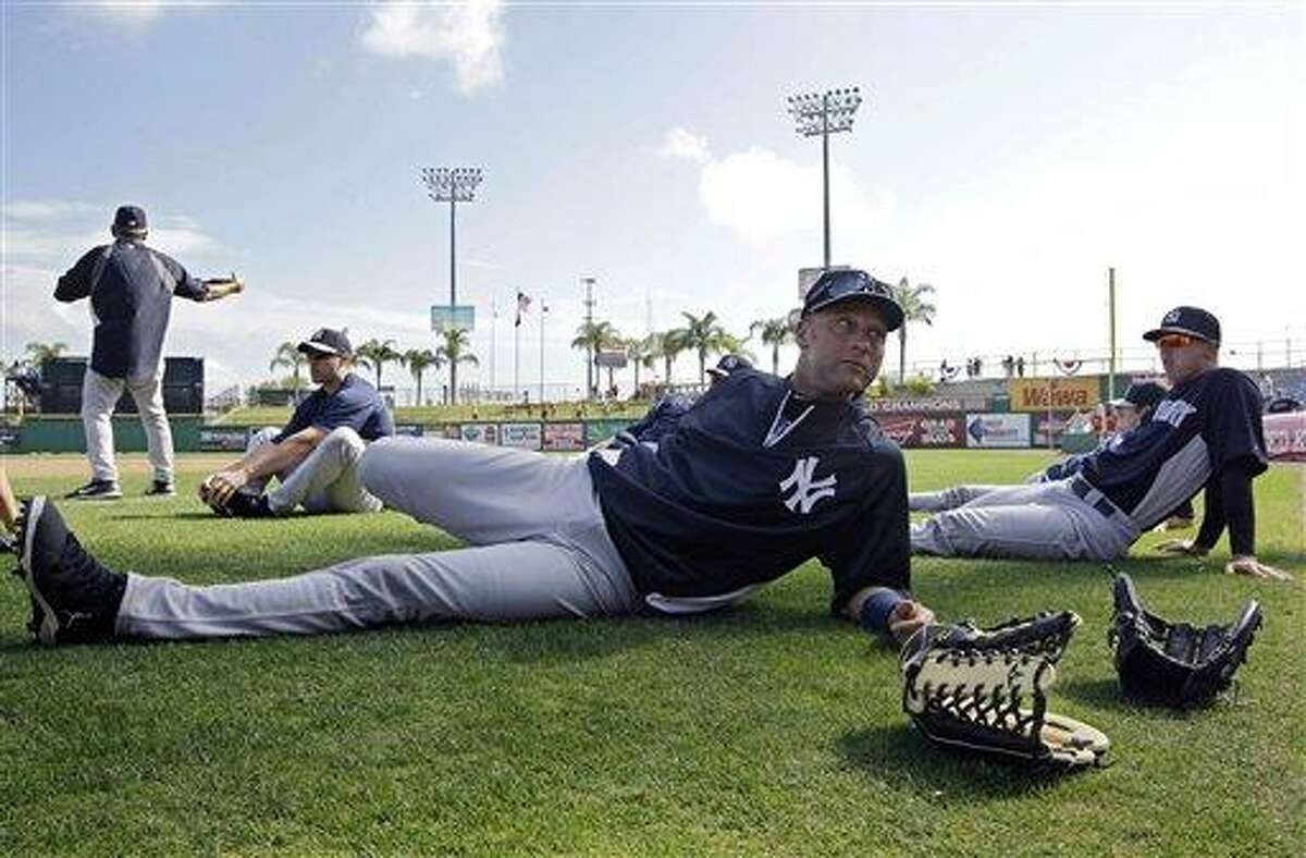 """New York Yankees shortstop Derek Jeter stretches before a spring training baseball game against the Philadelphia Phillies in Clearwater, Fla., Tuesday, March 19, 2013. Jeter says he was removed from Tuesday's lineup for """"precautionary"""" reasons because his surgically repaired left ankle feels """"stiff.""""(AP Photo/Kathy Willens)"""