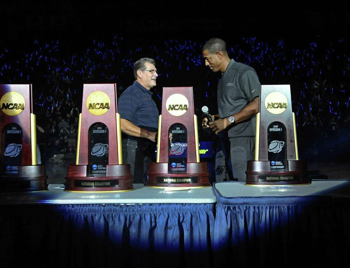UConn women's basketball coach Geno Auriemma, left, and men's coach Kevin Ollie stand with the 13 national championship trophies won by the two programs since 1995 during the Huskies' First Night festivities on Friday in Storrs.