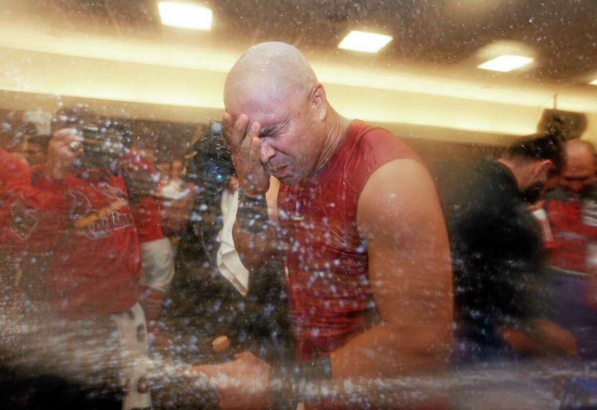 The St. Louis Cardinals' Carlos Beltran wipes sparkling wine off his face as the Cardinals celebrate a 6-1 win over the Pittsburgh Pirates in Game 5 of the National League division series on Wednesday. The Cardinals advanced to the NL championship series against the Los Angeles Dodgers.